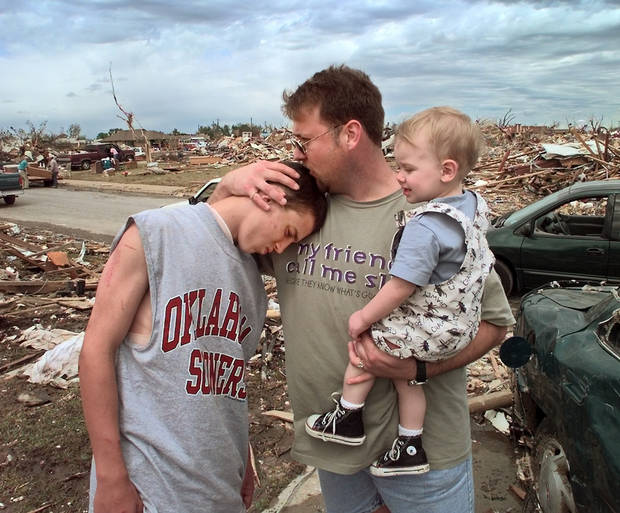 MAY 3, 1999 TORNADO: Tornado victims, damage: Brian Coburn, 14, son of Esther Coburn who was killed during Monday night's tornado in Moore, is given a hug by his older cousin Rick Lambert and his son Austin, both are from Dallas.