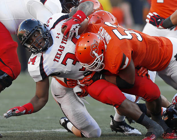 Oklahoma State's Ryan Simmons (52) brings down Texas Tech's Kenny Williams (34) during a college football game between Oklahoma State University (OSU) and Texas Tech University (TTU) at Boone Pickens Stadium in Stillwater, Okla., Saturday, Nov. 17, 2012.  Photo by Bryan Terry, The Oklahoman