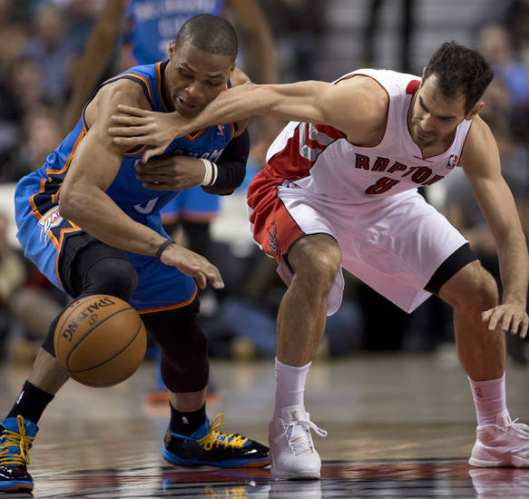Toronto Raptors guard Jose Calderon, right, and Oklahoma City Thunder guard Russell Westbrook battle for a loose ball during first-half NBA basketball game action in Toronto, Sunday, Jan.6, 2013. (AP Photo/The Canadian Press, Frank Gunn) ORG XMIT: FNG103