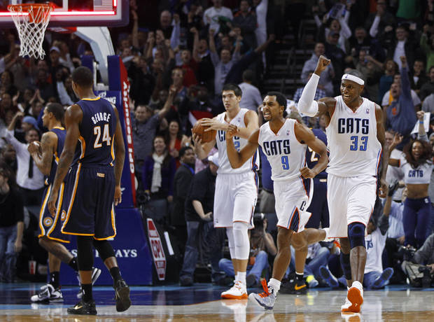 Charlotte Bobcats' Brendan Haywood (33) and Gerald Henderson (9) react as Indiana Pacers' Paul George (24) walks off the court at the end of an NBA basketball game in Charlotte, N.C., Friday, Nov. 2, 2012. The Bobcats won 90-89. (AP Photo/Chuck Burton)