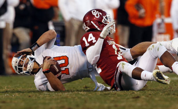 Oklahoma State's Clint Chelf (10) is sacked by Oklahoma's Aaron Colvin (14) during the second half of the Bedlam college football game in which  the University of Oklahoma Sooners (OU) defeated the Oklahoma State University Cowboys (OSU) 51-48 in overtime at Gaylord Family-Oklahoma Memorial Stadium in Norman, Okla., Saturday, Nov. 24, 2012. Photo by Steve Sisney, The Oklahoman