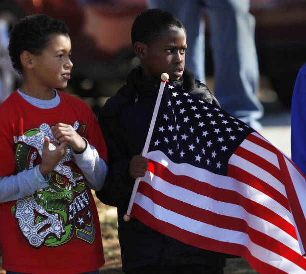 Boys from Soldier Creek Elementary School stand along Douglas Blvd. to watch the parade as it passes in front of their school. The city of Midwest City teamed with civic leaders and local merchants to display their appreciation for veterans and active military forces by staging a hour-long Veteran's Day parade that stretched more than a mile and a half along three of the city's busiest streets Monday morning, Nov. 12, 2012. Hundreds of people lined the parade route, many of them waving small American flags that had ben distributed by volunteers who marched near the front of the parade. A fly-over performed by F-16s from the138th Fighter Wing, Oklahoma Air National Guard unit in Tulsa thrilled spectators. Five veterans representing military personnel who served in five wars and military actions served as  Grand Marshals for the parade. Leading the parade was the Naval Reserve seven-story American flag, carried by 100 volunteers from First National Bank of Midwest City, Advantage Bank and the Tinker Federal Credit Union. The flag is 50 feet by 76 feet, weighs 110 pounds and was sponsored by the MWC Chapter of Disabled American Veterans. Photo by Jim Beckel, The Oklahoman