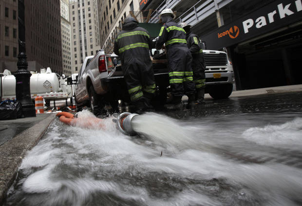Water is pumped from a subterranean parking garage in New York's Financial District, Friday, Nov. 2, 2012. Sandy, the storm that made landfall Monday, caused multiple fatalities, halted mass transit and cut power to more than 6 million homes and businesses.(AP Photo/Richard Drew) ORG XMIT: NYRD121