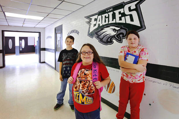 From left, former Farris students Jaden, sixth grade, Regina, third grade,  and Cheyenne, fifth grade, in one of the hallways in their new school, Lane School.  About 50 students transferred to Lane Public School after their former school, Farris School, was annexed by Lane in Atoka County.   Photo taken  March 1, 2013. Photo by Jim Beckel, The Oklahoman