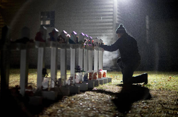 Frank Kulick, adjusts a display of wooden crosses, and a Jewish Star of David, representing the victims of the Sandy Hook Elementary School shooting, on his front lawn, Monday, Dec. 17, 2012, in Newtown, Conn. (AP Photo/David Goldman)