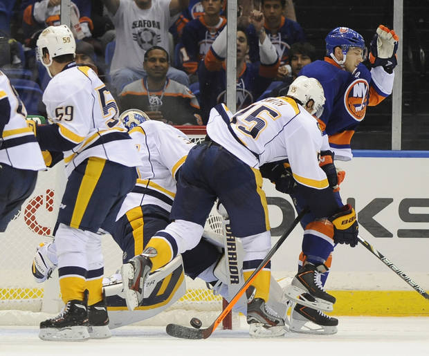 New York Islanders defenseman Matt Donovan, right,celebrates after shooting the puck past Nashville Predators goalie Pekka Rinne to score in the second period of a preseason NHL hockey game Friday, Sept. 27, 2013, in Uniondale, N.Y. (AP Photo/Kathy Kmonicek)