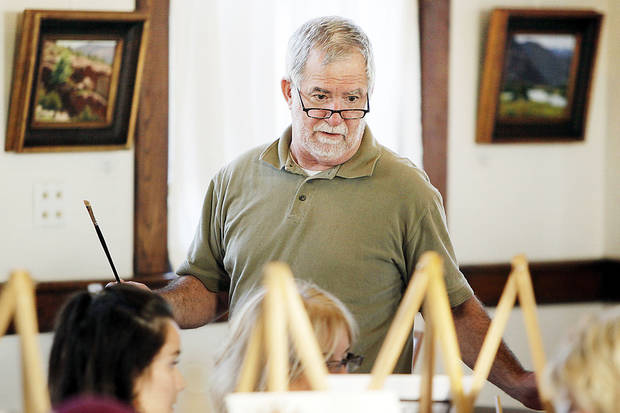 Artist Rick Fry checks on the progress of participants in the �Corkscrews and Canvas� painting party.