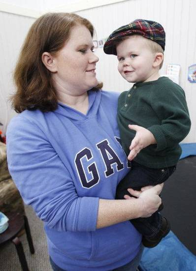 Candi Smithson holds her son, Preston, 2, on Wednesday at their home in Yukon. Smithson said a Pizza Hut in Muskogee made them leave because she brought in outside food for Preston, who has food allergies. Photo by Steve Gooch, The Oklahoman