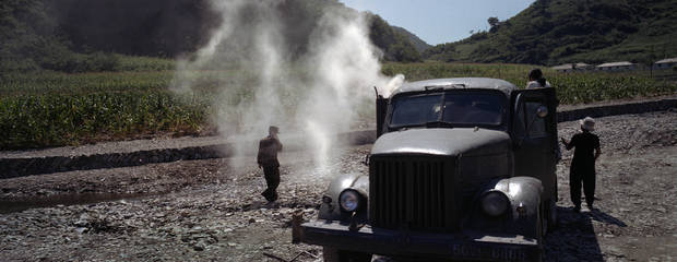 In this Aug. 13, 2012 photo, North Koreans try to move a truck, retrofitted to run on a barrel of burning wood, in a riverbed near Ungok, North Korea, during operations to aid victims of heavy flooding. (AP Photo/David Guttenfelder)