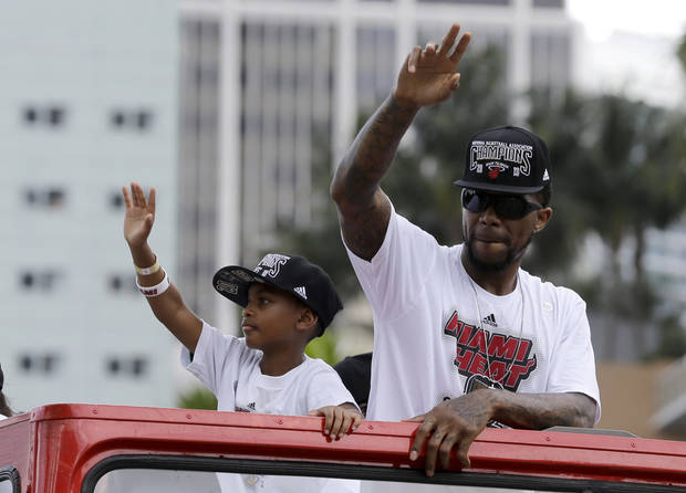 NBA champion Miami Heat's Udonis Haslem, right,  acknowledges fans during a parade honoring the team in Miami, Monday, June 24, 2013.  (AP Photo/Alan Diaz)
