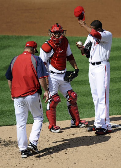 Washington Nationals pitching coach Steve McCatty, left, approaches catcher Kurt Suzuki and starting pitcher Edwin Jackson after a three-run home run by St. Louis Cardinals shortstop Pete Kozma in the second inning of Game 3 of the National League division baseball series on Wednesday, Oct. 10, 2012, in Washington. (AP Photo/Nick Wass)
