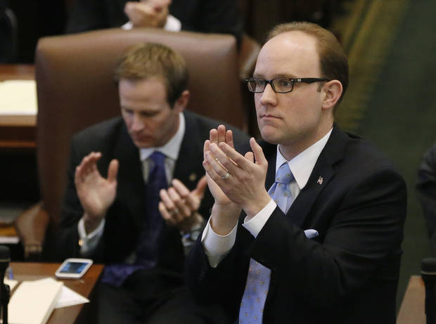 Oklahoma state Rep. Scott Inman, D-Oklahoma City, stands and applauds during Gov. Mary Fallin's State of the State address in Oklahoma City, Monday, Feb. 4, 2013. (AP Photo/Sue Ogrocki) ORG XMIT: OKSO110