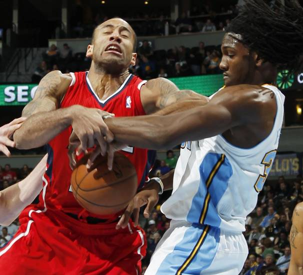 Atlanta Hawks guard Dahntay Jones, left, loses control of the ball as Denver Nuggets forward Kenneth Faried reaches in for the ball in the first quarter of an NBA basketball game in Denver on Monday, March 4, 2013. (AP Photo/David Zalubowski)