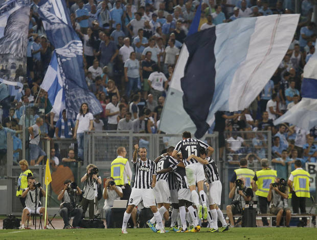 Juventus' Carlos Tevez, hidden, is celebrated by teammates after scoring during the Italian Supercup soccer match against Lazio at the Rome Olympic stadium Sunday, Aug. 18, 2013. (AP Photo/Gregorio Borgia)