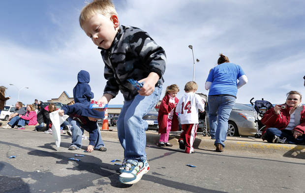 Matthew James, 3, picks up candy thrown by participants in the 89er Day Parade on Saturday, April 20, 2013 in Norman, Okla.  Photo by Steve Sisney, The Oklahoman