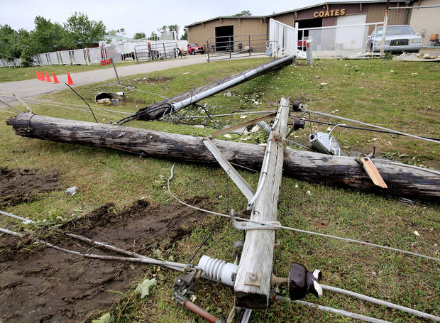 Snapped utility poles clutter the ground in front of Coates Roofing Co. on State Highway 99 in Seminole, Tuesday, May 11, 2010.  Numerous homes and business, including the town's airport, were damaged in  tornado that hit the community, located about 50 miles east of Oklahoma City,  Monday night.  Photo by Jim Beckel, The Oklahoman