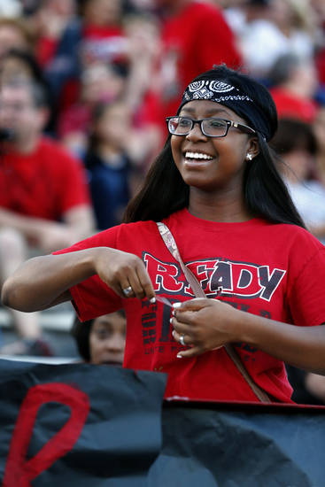 Carl Albert High School senior Tara Satterwhite tapes a banner to the stands before a high school football game between the Carl Albert Titans and the Deer Creek Antlers. Photo by Steve Sisney, The Oklahoman <strong>Steve Sisney - STEVE SISNEY</strong>