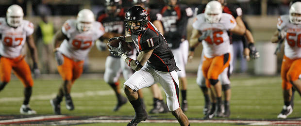 Texas Tech's Tramain Swindall (11) pulls in a reception in the Oklahoma State secondary during the second half of the college football game between the Oklahoma State University Cowboys (OSU) and the Texas Tech Red Raiders at Jones AT&T Stadium on Saturday, Nov. 8, 2008, in Lubbock, Tex.