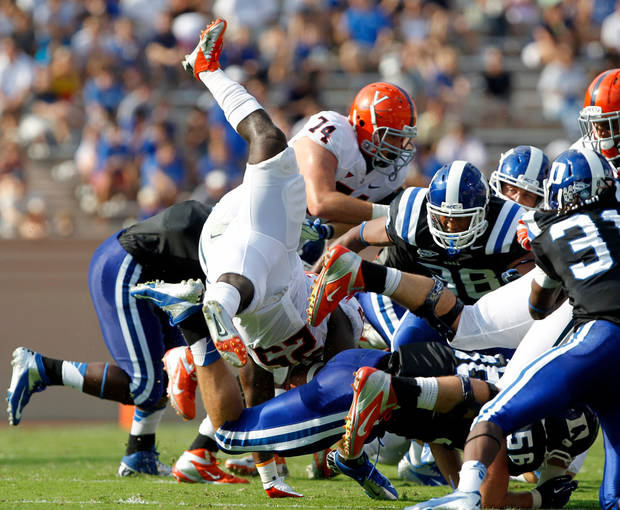 Duke defense upends Virginia running back Kevin Parks (25) during the second quarter of an ACC college football game at Wallace Wade Stadium in Durham N.C., on Saturday, Oct. 6, 2012. (AP Photo/The News & Observer, Chris Seward)