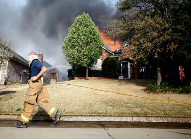 A firefighter runs past a house as it burns in the Oakwood East neighborhood in Midwest City, Okla., Thursday, April 9, 2009. Photo by Bryan Terry, The Oklahoman