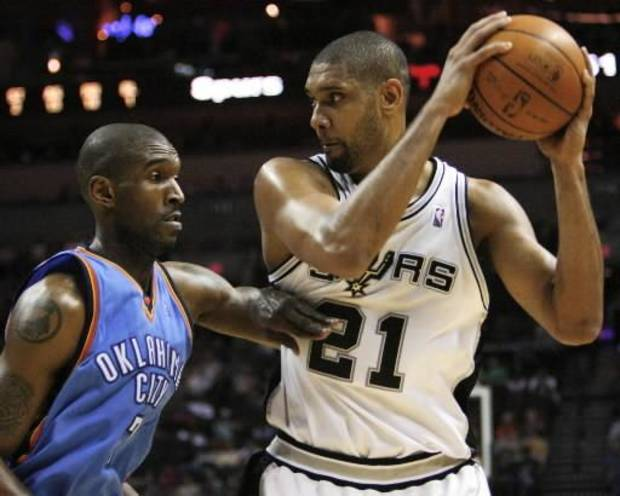 San Antonio Spurs forward Tim Duncan (21) keeps the ball away from Oklahoma City Thunder forward  Joe  Smith during the first half of an NBA basketball game on Sunday, Dec. 14, 2008, in San Antonio. (AP Photo/Darren Abate) 