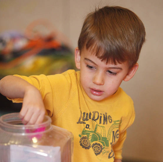 Left: Robbie Ley, 3, pulls a feather out of a bucket of craft items during an Easter crafts class sponsored by the Edmond Parks and Recreation Department. Photos by Paul Hellstern,  The Oklahoman