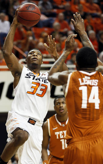 Oklahoma State's Marcus Smart (33) shoots between Texas' Jonathan Holmes (10) and Texas' Julien Lewis (14) during a men's college basketball game between Oklahoma State University (OSU) and the University of Texas at Gallagher-Iba Arena in Stillwater, Okla., Saturday, March 2, 2013. Photo by Nate Billings, The Oklahoman