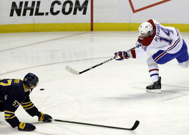 Montreal Canadiens' Tomas Plekanec (14), of the Czech Republic, shoots and scores under pressure from Buffalo Sabres' Tyler Myers (57) during the first period of an NHL hockey game in Buffalo, N.Y., Thursday, Feb. 7, 2013. (AP Photo/David Duprey)