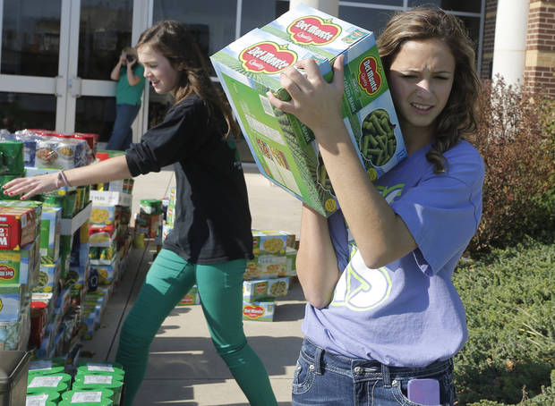 Addie Plank helps load food collected for the Regional Food Bank of Oklahoma at Bishop McGuinness High School Friday, November 9, 2012.  The school collected 75,660 pounds of food. Photo by Doug Hoke, The Oklahoman