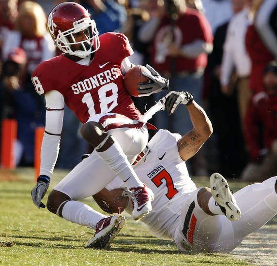 Oklahoma State's Shamiel Gary (7) drags Jalen Saunders (18) down after a reception during the Bedlam college football game between the University of Oklahoma Sooners (OU) and the Oklahoma State University Cowboys (OSU) at Gaylord Family-Oklahoma Memorial Stadium in Norman, Okla., Saturday, Nov. 24, 2012. Photo by Steve Sisney, The Oklahoman