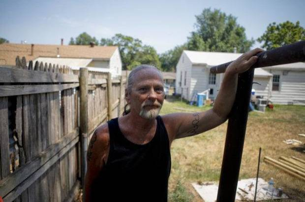 Dale Osborne stands in his neighbor's backyard while volunteers from the Catholic HEART Workcamp repair his fence. Volunteers are helping Osborne and his neighbors this week in the Riverpark neighborhood in southwest Oklahoma City. <strong>ZACH GRAY - THE OKLAHOMAN</strong>