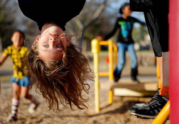 Kammi Burgess, 7, hangs upside down on playground equipment at the Boys and Girls Club in Oklahoam City, Thursday, March 1, 2012. Photo by Bryan Terry, The Oklahoman