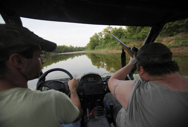 Johnny Heskett and Josh Kinsey drive along a river, looking for places to set up traps, during a recent feral hog hunting trip near Indianola. Photos by Garett Fisbeck, The Oklahoman