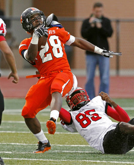 Norman's Donovan Roberts (28) is pulled down after a long gain by Steffon Herd (85) as the Norman High School Tigers play the Del City Eagles on Thursday, September 15, 2011, in Norman, Okla.   Photo by Steve Sisney, The Oklahoman