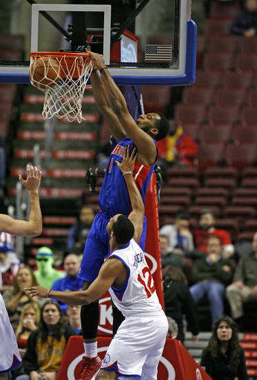 Detroit Pistons' Andre Drummond (1) scores as Philadelphia 76ers' Evan Turner (12) defends in the first half of an NBA basketball game Wednesday Nov. 14, 2012 in Philadelphia. (AP Photo/ H. Rumph Jr)