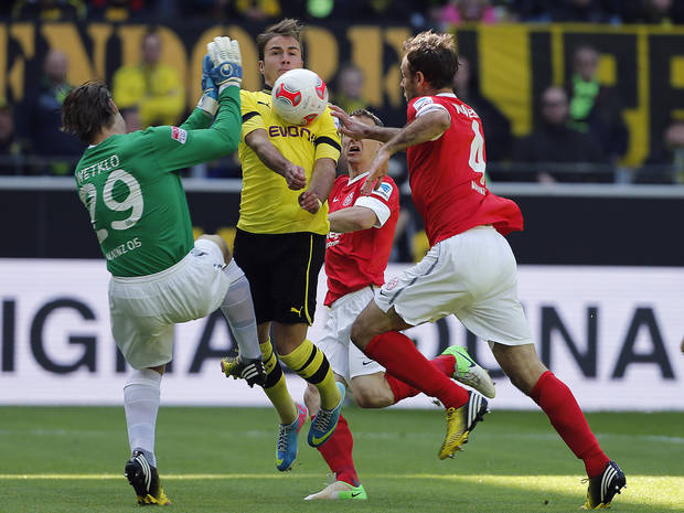 Mainz goalkeeper Christian Wetklo, from left, Dortmund's Mario Goetze and Mainz's Nikolce Noveski of Macedonia challenge for the ball during the German first division Bundesliga soccer match between Borussia Dortmund  and FSV Mainz 05 in Dortmund, Germany, Saturday, April 20, 2013. (AP Photo/Frank Augstein)