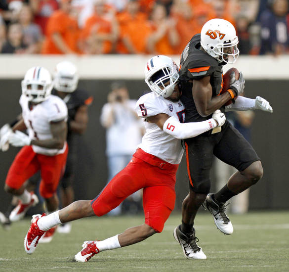 Oklahoma State's Justin Blackmon fights off Arizona's Shaquille Richardson during the first half of their game in Stillwater on Thursday. PHOTO BY BRYAN TERRY, The Oklahoman