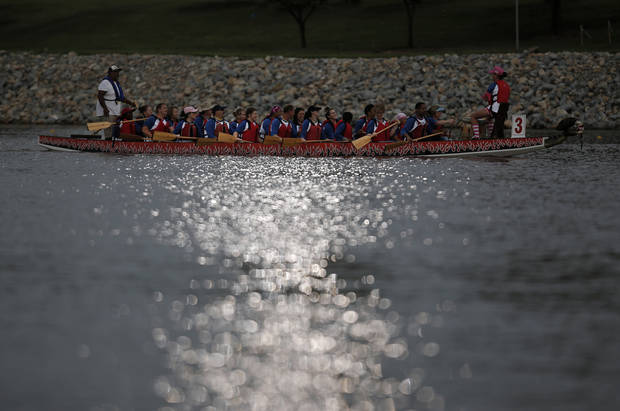 A dragon boat paddles down the Oklahoma River during the Oklahoma Regatta Festival Night Sprints in Oklahoma City, Thursday, Sept. 27, 2012.  Photo by Garett Fisbeck, The Oklahoman