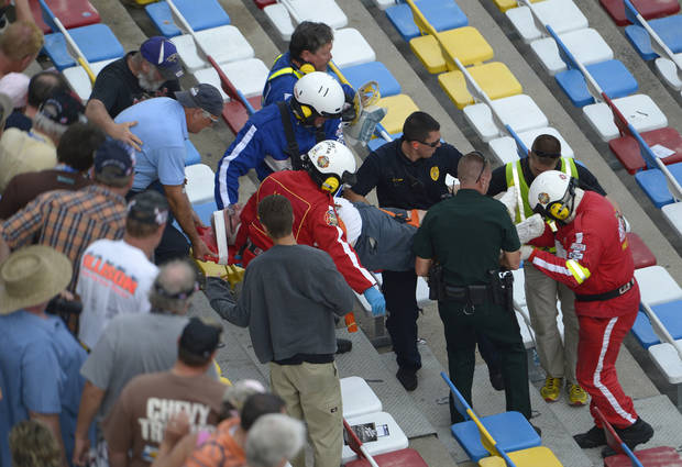 Emergency officials transport an injured spectator from the grandstands after Kyle Larson's car hit the safety wall and fence along the front stretch on the final lap of the NASCAR Nationwide Series auto race at Daytona International Speedway in Daytona Beach, Fla., Saturday, Feb. 23, 2013. Larson's car hit the safety fence sending car parts and other debris flying into the stands injuring spectators. (AP Photo/Phelan M. Ebenhack)