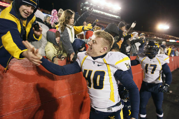 West Virginia kicker Tyler Bitancurt celebrates with fans after a 31-24 victory over Iowa State in an NCAA college football game on Friday, Nov. 23, 2012, in Ames, Iowa. (AP Photo/Matthew Putney)