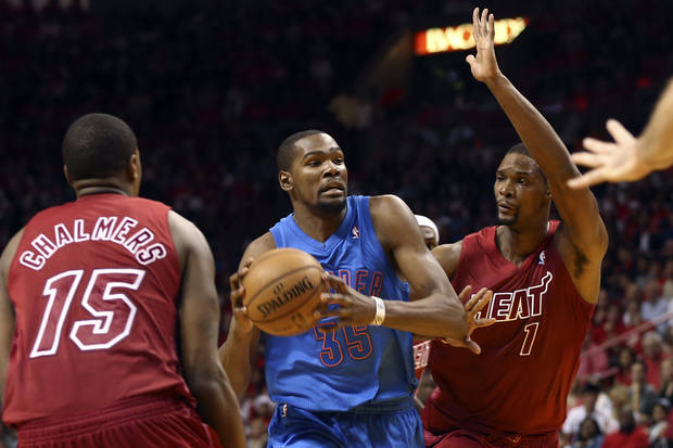 Miami Heat's Mario Chalmers (15) and Chris Bosh (1) defend against Oklahoma City Thunder's Kevin Durant during the second half of an NBA basketball game in Miami, Tuesday, Dec. 25, 2012. The Heat won 103-97. (AP Photo/J Pat Carter) ORG XMIT: FLJC113