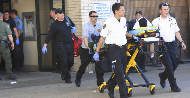 Medics wheel an injured man Saturday out of Arrowhead Mall in Muskogee.  AP PHOTO/The Daily Phoenix, Jerry Willis