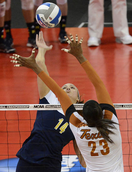 Michigan's Claire McElheny, facing, attempts to score over the defense of Texas' Bailey Webster during the national semifinals of the NCAA college women's volleyball tournament Thursday, Dec. 13, 2012 in Louisville, Ky. (AP Photo/Timothy D. Easley)