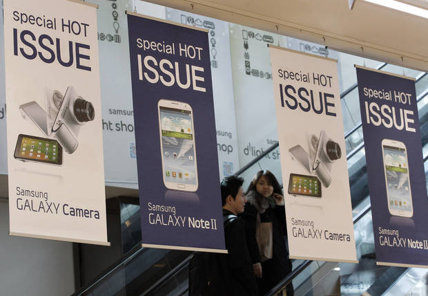 Banners advertising Samsung Electronics' Galaxy Note II and Galaxy Camera are displayed at the showroom of the company's headquarters in Seoul, South Korea, Friday, Jan. 25, 2013. Samsung Electronics Co. said quarterly profit soared 76 percent, boosted by the popularity of its Galaxy smartphones, which outsold the iPhone for a fourth straight quarter. But the company said Friday it expects earnings to decline during the current quarter because of seasonally low demand for consumer electronics. (AP Photo/Ahn Young-joon)