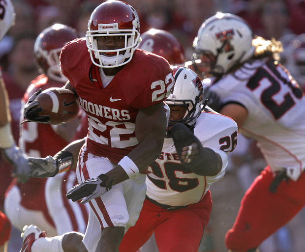 Oklahoma's Roy Finch (22) runs the ball up field past Texas Tech's Franklin Mitchem (26) during the first half of the college football game between the University of Oklahoma Sooners (OU) and the Texas Tech Red Raiders (TTU) at the Gaylord Family Memorial Stadium on Saturday, Nov. 13, 2010, in Norman, Okla.  Photo by Chris Landsberger, The Oklahoman