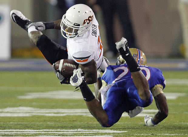 Oklahoma State's Jeremy Smith (31) is upended by Tulsa's Marco Nelson (20) during a college football game between the Oklahoma State University Cowboys and the University of Tulsa Golden Hurricane at H.A. Chapman Stadium in Tulsa, Okla., Sunday, Sept. 18, 2011. Photo by Chris Landsberger, The Oklahoman