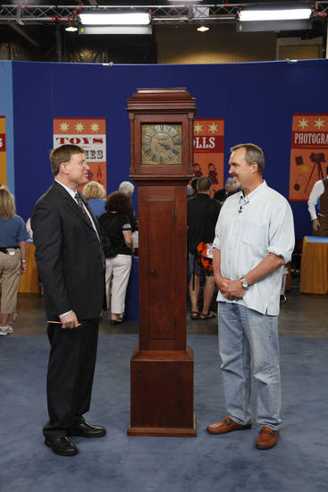 Gary Sullivan, left, a featured appraiser on PBS�s �Antiques Roadshow,� specializes in high-end, American antiques and clocks. Here he talks with a guest about an Isaac Jackson Tall Case Clock, circa 1760.  Photo courtesy of WGBH by Jeff Dunn