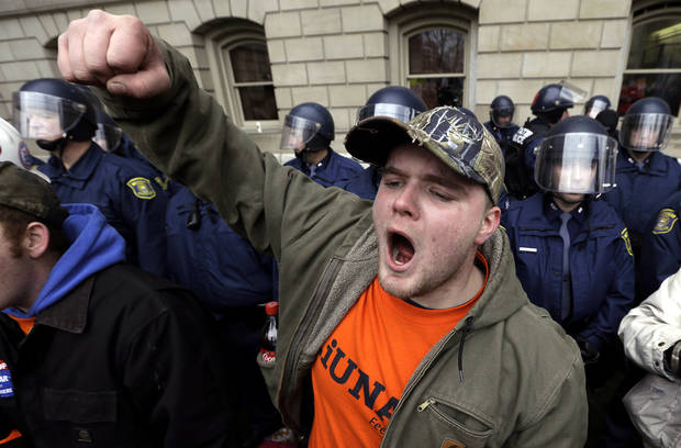 Drew Dobson, of Coleman, Mich., protests at a rally at the State Capitol in Lansing, Mich., Tuesday, Dec. 11, 2012. The crowd is protesting right-to-work legislation passed last week. Michigan could become the 24th state with a right-to-work law next week. Rules required a five-day wait before the House and Senate vote on each other&#039;s bills; lawmakers are scheduled to reconvene Tuesday and Gov. Snyder has pledged to sign the bills into law. (AP Photo/Paul Sancya)p