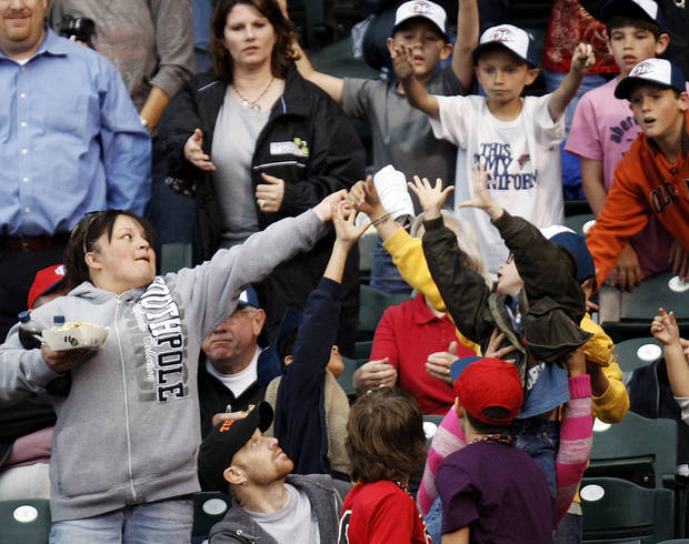 Fans try to catch a t-shirt thrown in the stands before the 2012 opening day baseball game between the Oklahoma City RedHawks and the Memphis Redbirds at the Chickasaw Bricktown Ballpark in Oklahoma City, Thursday, April 5, 2012. Photo by Nate Billings, The Oklahoman