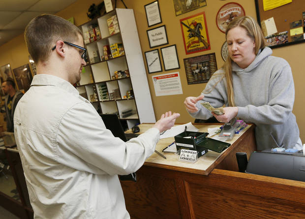 Melissa Burger, co-owner of Locked and Loaded in Choctaw, sells a 15-round magazine for a handgun to Dave Therio. Therio said he is in the process of getting his concealed carry permit. Photo by Nate Billings, The Oklahoman